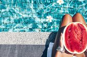 Girl holding watermelon in the blue pool, slim legs, instagram style. Tropical fruit diet. Summer ho poster