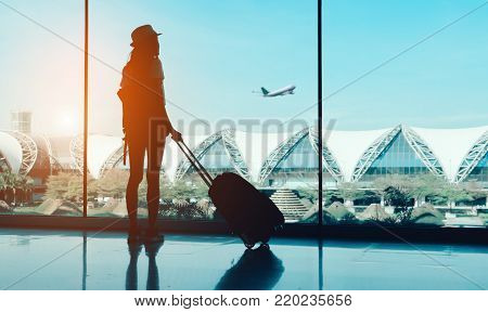 poster of Silhouette woman travel with luggage looking without window at airport terminal international or girl teenager traveling in vacation summer relaxation holding suitcase and backpack