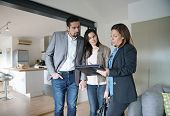 Couple with real-estate agent visiting modern house poster