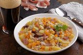 Traditional Irish dish Dublin coddle with sausages and beer on a table poster