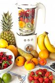 Abundance of fruit around a blender for making smoothies