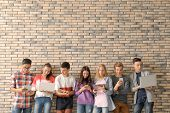 Group of cool teenagers with modern devices near brick wall poster