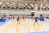 Blurred Teen Girls Playing Indoor Volleyball poster