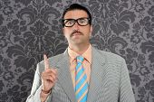 nerd retro teacher raising finger up over vintage wallpaper background