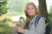 Woman examining leaf with magnifying glass
