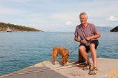 hombre con su perro sentado en el puerto