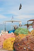 stock photo of epidavros  - Greek fishing nets and boat in harbor from Nea Epidavros - JPG