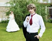 stock photo of glans  - Portrait of a young bride in nature in a dark suit and red tie - JPG