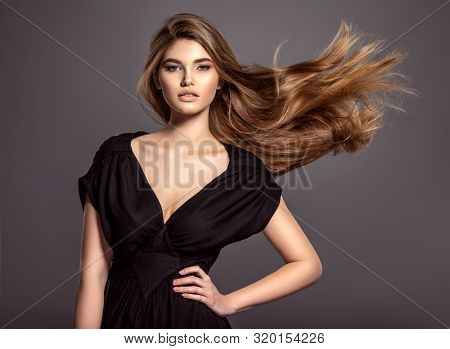 poster of Woman with beauty long brown hair.  Beautiful face of an attractive  model with blue eyes. Closeup p