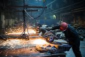 Grinding In A Steel Factory. Worker With A Big Saw Cutting Metal. poster