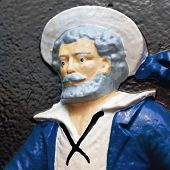 A painted figure of a sailor on a cast iron plaque.  Plaque is found in the Halifax Public Gardens in Halifax, Nova Scotia, Canada.