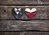 Symbolic male and female heart shapes. On old vintage wooden background. Wedding or st.Valentine theme.