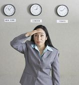 Hispanic businesswoman under wall clocks