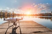 Drone copter with digital camera, blur river on background poster