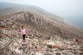A Young Girl Tourist Stands On The Edge Of A High Cliff On The Shore Of Lake Baikal. Girl Looking At poster