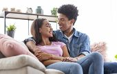 Romantic African American Teens Having Rest At Home, Embracing On Couch And Glancing To Each Other poster