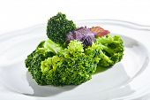 Macro shot of steamed broccoli on white restaurant plate isolated. Green asparagus cabbage cooked on poster