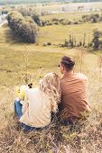 Back View Of Woman With Bouquet And Man Sitting Outside poster
