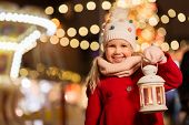 holidays, childhood and people concept - happy little girl with lantern at christmas market in winte poster