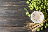 Mag With Beer, Spikelets And Hop On Wooden Table, Top View poster