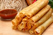 pic of flauta  - Stack of chicken taquitos with hot sauce and sour cream in kitchen or restaurant - JPG
