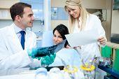 Dentista mostrando radiografia e explicar ao paciente e assistente