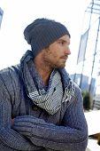 Retrato ao ar livre, de cara na moda vestindo o lenço e chapéu, braços cruzados.