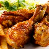 stock photo of grill  - Grilled chicken legs with chips and vegetables - JPG