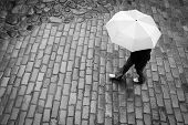 stock photo of cobblestone  - Woman with umbrella in rain old town - JPG