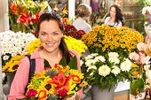 Cheerful florist woman showing colorful flowers market shop retail