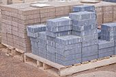 Stacks of various colored concrete pavers (paving stone) or patio blocks organized on wooden pallets