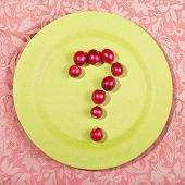 Ripe cranberries forming a question mark on a green plate.