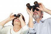 Casal de idosos olha através de binóculos