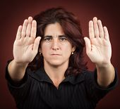 pic of racial discrimination  - Serious hispanic woman with her two hands extended signaling to stop  - JPG