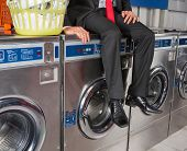 Low section of businessman with laundry basket sitting on washing machine at laundromat