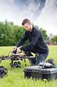 Young engineer assembling UAV helicopter in park