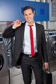 Portrait of smart young businessman with suitcase and suitcover in laundry
