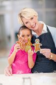 stock photo of granddaughters  - happy senior woman and granddaughter holding gingerbread cookies they just baked - JPG