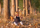 Sweet girl playing with autumn leaf