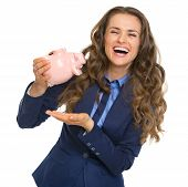 Smiling Business Woman Shaking Out Coins From Piggy Bank