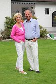 picture of manicured lawn  - Successful contented senior couple standing close together on a manicured green lawn in font of their home smiling at the camera - JPG