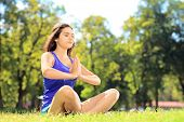 pic of stressless  - Young female athlete in sportswear doing yoga exercise seated on a grass in a park - JPG