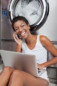 Portrait of happy young African American woman with laptop using mobilephone in laundry