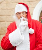 Portrait of Santa Claus with finger on lips standing outside house