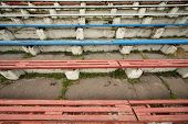 Long dirty destroyed blue and red grandstands at old stadium.