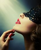 Beautiful Woman with Black Lace mask over her Eyes. Red Sexy Lips and Nails closeup. Open Mouth. Man