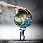 Image of young businessman under pressure of planet Earth. Elements of this image are furnished by N