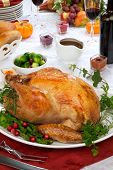 foto of horn plenty  - Garnished roasted turkey on fall festival decorated table with horn of plenty and red wine