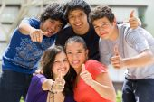 stock photo of ethnic group  - Multi ethnic teenagers posing outside school building - JPG