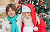 Portrait of boy with arm around Santa Claus against decorated Christmas tree outdoors